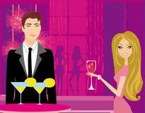 年轻夫妇挥动并且喝在俱乐部的香槟 库存图片