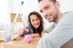 年轻夫妇挽救金钱在存钱罐中 免版税图库摄影