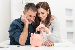 夫妇挽救金钱 免版税库存图片