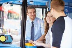 年轻夫妇搭乘公共汽车和购买票 免版税图库摄影