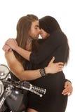 夫妇摩托车亲吻的几乎穿戴黑色 图库摄影