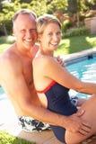 夫妇放松庭院的池 库存图片