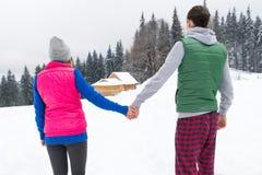 年轻夫妇斯诺伊村庄木乡间别墅男人和妇女冬天雪手段村庄 免版税库存图片