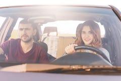 夫妇旅客在汽车的伸手可及的距离目的地:轮子的美丽的微笑的妇女教驾驶,她的丈夫坐在前座,继续 免版税库存照片