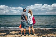 夫妇旅客站立在海滨和神色的男人和妇女在照相机冒险旅行旅途概念 免版税库存图片