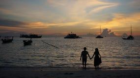 年轻夫妇日落剪影在爱的在海滩 免版税库存图片