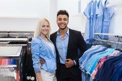 年轻夫妇时尚商店、愉快的微笑的人和选择衣裳礼服购物的妇女顾客 免版税库存照片