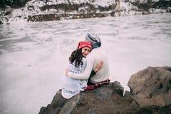 夫妇是拥抱和微笑反对冻湖背景  回到女孩查找 免版税库存图片