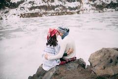 夫妇是拥抱和微笑反对积雪的小山和冻湖背景  免版税库存照片