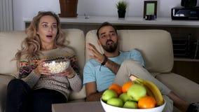 夫妇显露的射击在长沙发的在观看一个可怕恐怖片的客厅 股票录像
