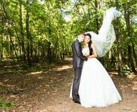夫妇最近结婚了 举长的白色新娘面纱的风 免版税图库摄影
