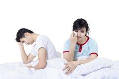 在战斗的哀伤的夫妇在床上以后 免版税库存照片