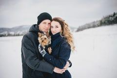 年轻夫妇有与他们的狗的步行在多雪的乡下 免版税库存照片