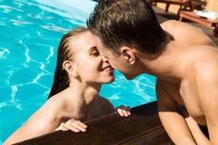 夫妇有休息在水池用香槟 他们微笑着,拥抱并且亲吻 免版税库存图片