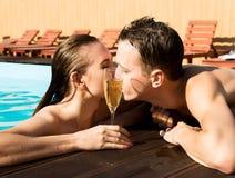 夫妇有休息在水池用香槟 他们微笑着,拥抱并且亲吻 免版税库存照片