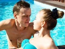 夫妇有休息在水池用香槟 他们微笑着,拥抱并且亲吻 库存照片