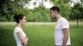 年轻夫妇有战斗在夏天公园,排在行或列中最末端之人离开妇女 慢的行动 股票录像