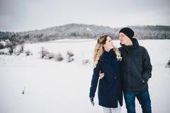 年轻夫妇有步行在多雪的乡下 库存图片