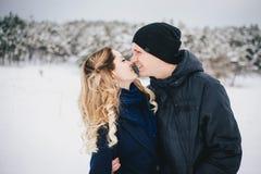 年轻夫妇有步行在多雪的乡下 免版税图库摄影
