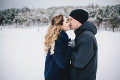 年轻夫妇有步行在多雪的乡下 免版税库存照片
