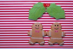 夫妇有omela的姜饼人在条纹背景离开 圣诞节姜饼人曲奇饼顶视图,文本空间 库存照片