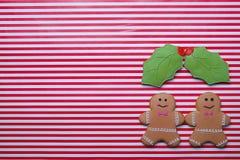 夫妇有omela的姜饼人在条纹背景离开 圣诞节姜饼人曲奇饼顶视图,文本空间 免版税库存照片