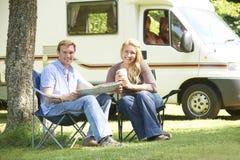 夫妇松弛外部住房汽车在度假 免版税库存照片