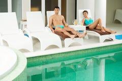 夫妇松弛近的游泳池 免版税图库摄影