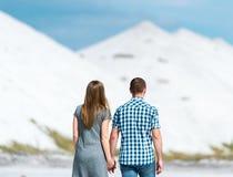 年轻夫妇步行沙漠地球上的 免版税库存照片