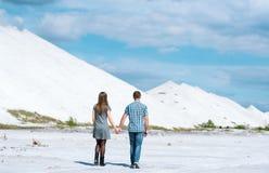 年轻夫妇步行沙漠地球上的 免版税库存图片