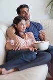 夫妇注意的电视的纵向,当吃玉米花时 库存图片