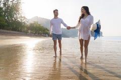 夫妇海滩暑假,爱的走美丽的年轻愉快的人,人握手的妇女微笑 免版税库存照片