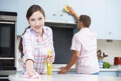 夫妇清洁一起厨房表面和碗柜 库存照片
