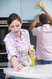 夫妇清洁一起厨房表面和碗柜 图库摄影