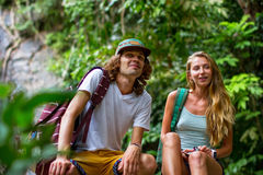 年轻夫妇游人基于岩石在密林 库存图片