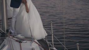 年轻夫妇特写镜头视图在婚礼的适合在游艇的板的身分 拥抱在晚上的新娘和新郎 股票录像