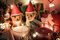 夫妇玩具熊、白色和紫罗兰色圣诞节蜡烛和装饰品装饰圣诞快乐和新年好 免版税库存图片