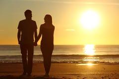 夫妇现出轮廓一起走在海滩 库存图片