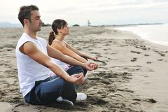 夫妇瑜伽海滩 免版税库存图片