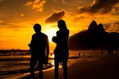 夫妇由在海滩的日落现出轮廓 免版税库存照片