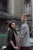 年轻夫妇由在街道上的手互相采取 免版税图库摄影