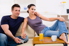 夫妇电视注意的年轻人 免版税库存照片
