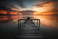 夫妇的剪影一起花费时间在日落期间在一只木跳船上 库存照片