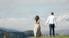 夫妇的美好的步行在山的多云天空下 股票录像