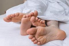 年轻夫妇的脚在床上一起睡觉 免版税库存照片