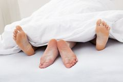 夫妇的脚特写镜头睡觉在床上的 免版税库存照片