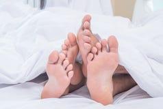 夫妇的脚肩并肩在床上 图库摄影