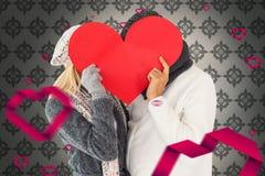 夫妇的综合图象在冬天塑造摆在与心脏形状 免版税库存图片