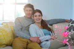 夫妇的综合图象在沙发和华伦泰心脏3d的 库存照片