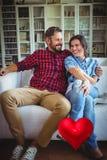 夫妇的综合图象在沙发和红色心脏3d的 免版税库存照片